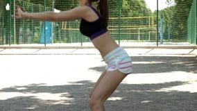 Sport dziewczyna w krótkich skrótach robi kucnięciom w lecie na sądzie zdjęcie wideo