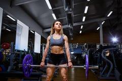 Sport dziewczyna z barbell w jej rękach w gym Obraz Stock