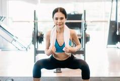Sport dziewczyna z sportswear robi kucnięciom na platformie w gym, napad Obraz Royalty Free