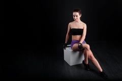Sport dziewczyny obsiadanie i patrzeć kamerę przeciw czarnemu tłu Fotografia Royalty Free