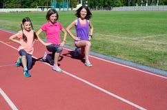 Sport e forma fisica della famiglia, madre felice e bambini esercitantesi e mantenere sulla pista dello stadio all'aperto, bambin fotografia stock libera da diritti