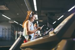 Sport e musica di tema Un bello funzionamento caucasico della donna nella palestra sulla pedana mobile Sulle grandi cuffie bianch Fotografia Stock Libera da Diritti