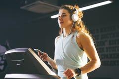 Sport e musica di tema Un bello funzionamento caucasico della donna nella palestra sulla pedana mobile Sulle grandi cuffie bianch Immagini Stock Libere da Diritti