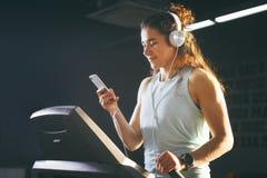 Sport e musica di tema Un bello funzionamento caucasico della donna nella palestra sulla pedana mobile Sulle grandi cuffie bianch Immagine Stock Libera da Diritti