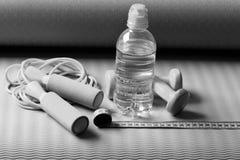sport e salute Concetto del rinfresco e di allenamento Bottiglia o acqua vicino alla corda di salto Fotografia Stock Libera da Diritti