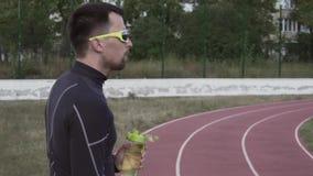 Sport e salute di tema Acqua potabile del giovane corridore maschio caucasico dell'atleta da una bottiglia di sport ad uno stadio archivi video