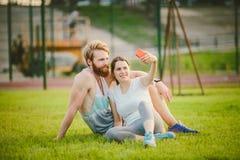 Sport e tecnologia Giovani nelle coppie caucasiche eterosessuali di amore che riposano dopo l'allenamento all'aperto nel parco su Fotografia Stock
