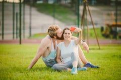 Sport e tecnologia Giovani nelle coppie caucasiche eterosessuali di amore che riposano dopo l'allenamento all'aperto nel parco su Fotografie Stock Libere da Diritti