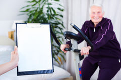 Sport effort tests. Geriatrician taking notes about the effort capacity of an elderly woman in a nursing home Royalty Free Stock Images