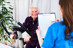 Sport effort tests - happy with the results. Geriatrician taking notes about the effort capacity of an elderly women in a nursing home royalty free stock image