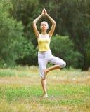 Sport, Eignung, Yoga - Konzept, Frau, die Übung tut Stockbild
