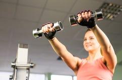 Sport-, Eignungs-, Bodybuilding-, Teamwork- und Leutekonzept - junge Frau, die Muskeln auf Turnhallenmaschine biegt Lizenzfreies Stockfoto
