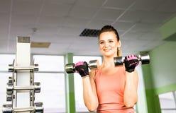 Sport-, Eignungs-, Bodybuilding-, Teamwork- und Leutekonzept - junge Frau, die Muskeln auf Turnhallenmaschine biegt Stockfotos