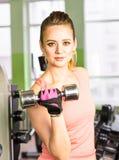 Sport-, Eignungs-, Bodybuilding-, Teamwork- und Leutekonzept - junge Frau, die Muskeln auf Turnhallenmaschine biegt Stockfotografie