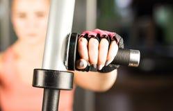 Sport-, Eignungs-, Bodybuilding-, Teamwork- und Leutekonzept - junge Frau, die Muskeln auf Turnhallenmaschine biegt Lizenzfreie Stockfotografie