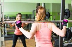 Sport-, Eignungs-, Bodybuilding-, Teamwork- und Leutekonzept - junge Frau, die Muskeln auf Turnhallenmaschine biegt Lizenzfreie Stockbilder