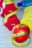 Sport-, Eignungs-, Diät- und Gegenstandkonzept - nah oben vom Dummkopf und vom roten Apfel mit messendem Band Stockfotos