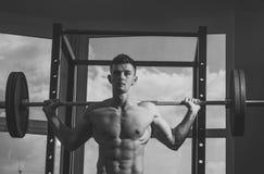 Sport en gymnastiekconcept De mens met torso, spiermacho oefent met barbell, venster op achtergrond uit sportsman royalty-vrije stock foto