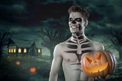 Sport en natuurlijke voeding, Halloween-pompoen Jonge mens met spierlichaam en pompoen Sterk mensenlichaam Naakt concept Het conc royalty-vrije stock fotografie