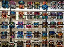 Sport equipment background. Colored snowboard masks in a rows on a showcase. Colorful ski masks on the shop window in royalty free stock images