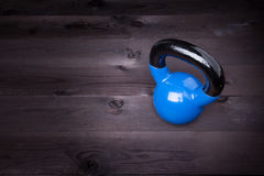 Sport equipment. Blue kettle bell on a black wooden background Stock Image