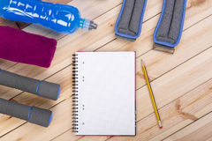 Sport Equipment. Dumbbells, Drink, Notebook. Stock Photo