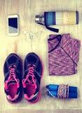 Sport equipment on floor. Set of sportswear and accessories on wooden floor. Girlish sport equipment Stock Images