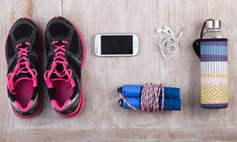 Sport equipment on floor. Set of sportswear and accessories on wooden floor. Top view of girlish sport equipment Stock Photography