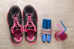 Sport equipment on floor. Top view of sport equipment set and energy drink smoothie on wooden floor Royalty Free Stock Images
