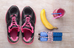 Sport equipment on floor. Top view of set of sport equipment and energy food and drink on wooden floor Royalty Free Stock Photo