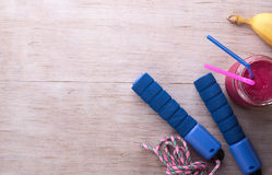 Sport equipment on floor. Top view of sport equipment set and energy food and drink on wooden floor Royalty Free Stock Photography