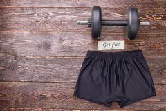 Sport equipment for muscle training. Athletic shorts and barbell, wooden background. Sport as lifestyle Royalty Free Stock Images