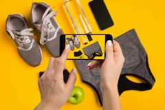 Sport equipment photographing on mobile phone. Smartphone screen with fitness tools image. Made for social networks Stock Photos