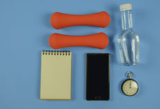 Sport equipment. Sport shoes, Sport equipment and bottle of water on blue background Royalty Free Stock Photos