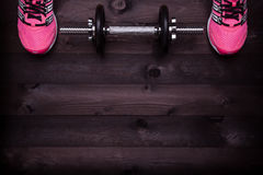 Sport equipment. Sneakers and a dumbbell on a black wooden background Royalty Free Stock Photos