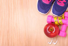Sport equipment. Sneakers, dumbbells, measuring tape, apple Stock Image