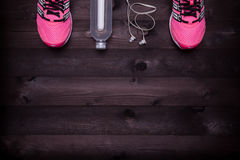Sport equipment. Sneakers, water and earphones on a black wooden background Royalty Free Stock Photography