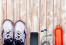 Sport equipment. Sneakers, water, earphones and phone on wooden Royalty Free Stock Photos