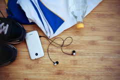 Sport equipment. Sneakers, water, earphones and phone on wooden Stock Photos