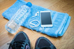Sport equipment. Sneakers, water , earphones, smart phone Royalty Free Stock Photo