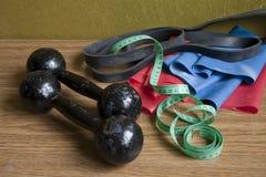 Sport equipment on the floor- dumbbells and resistance bands. Sport equipment on the wooden floor- dumbbells and resistance bands Stock Images