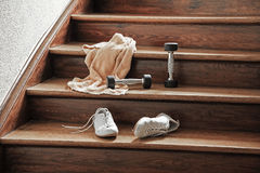 Sport equipments towel barbells trainers left on wooden stairs Stock Photos
