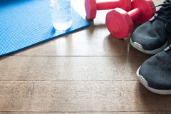 Sport equipments on wooden floor and red dumbbells Royalty Free Stock Photography