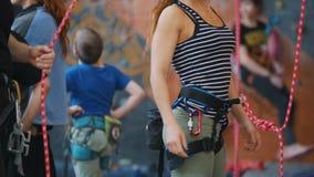Sport estremo, bouldering L'istruttore aiuta la donna a mettere sopra le corde della protezione video d archivio