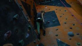 Sport estremo Una giovane donna che va giù da una parete rocciosa all'interno video d archivio