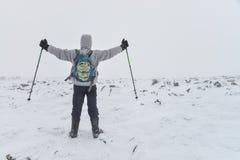 Sport estremo Viandante sola in montagne di inverno che stanno alla cima con i hads su sollevati Fotografia Stock