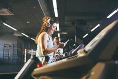 Sport et musique de thème Une belle femme caucasienne courant dans le gymnase sur le tapis roulant Sur de grands écouteurs blancs Photographie stock libre de droits