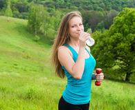 Sport, exercise and healthcare - sporty girl with water bottle. Young beautiful woman drinking water after fitness exercise outdoo Royalty Free Stock Images