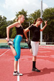 Sport exercises. Two young girls doing stretching exercises Stock Photography