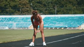 Sport, exercises outdoors. Girl doing stretching on stadium. Bending aside. Full body, looking aside stock video footage